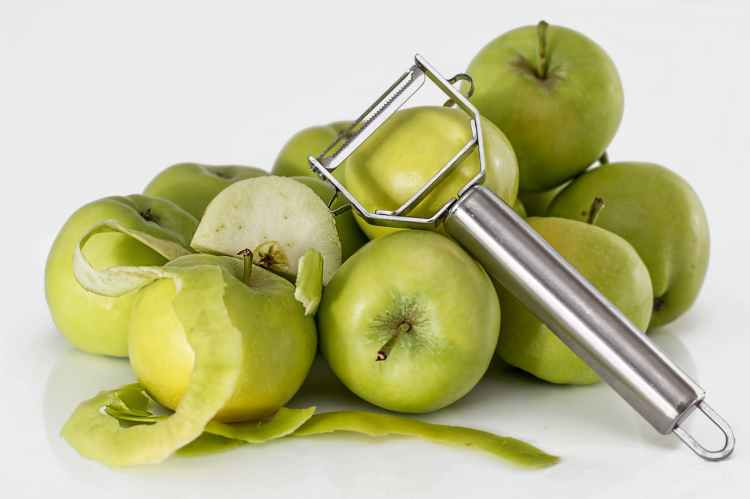 green unripe apple with silver peeler