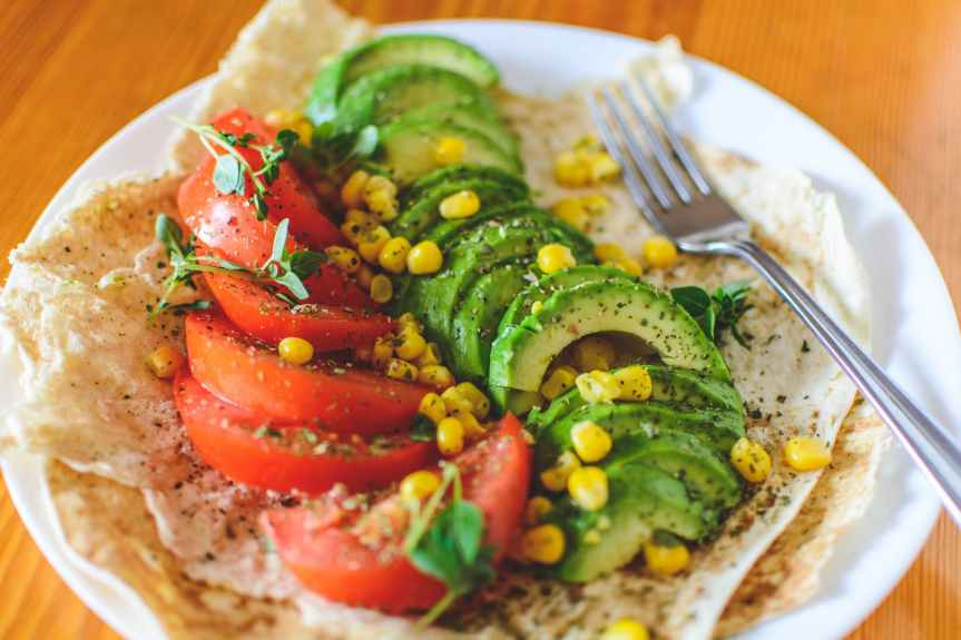 sliced tomato and avocado on white plate
