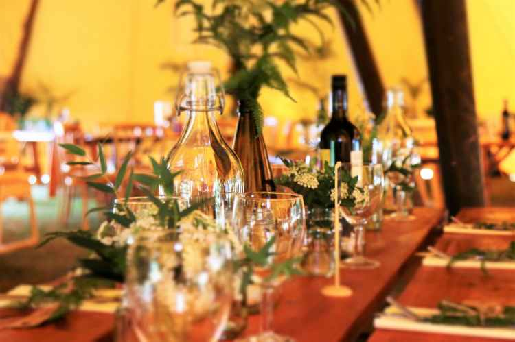 wine glasses and wine bottles on top of brown wooden table