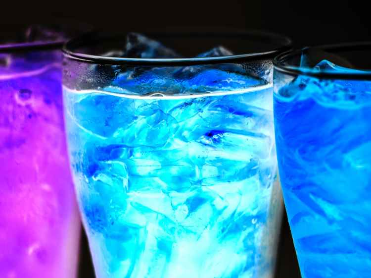 three lighted cocktails inside drinking glasses